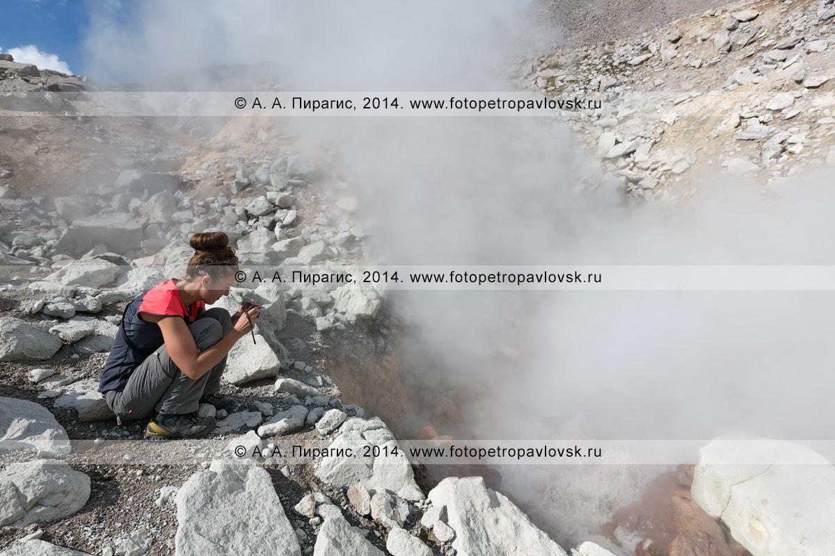 Фотография: девушка — турист и путешественник фотографирует фумаролы камчатского вулкана Дзензур (Dzenzur Volcano). Камчатка, Дзензур-Жупановская группа вулканов