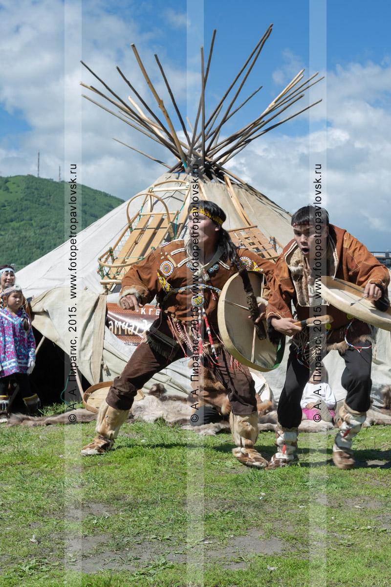 Фотография: мужчины в традиционной одежде коренных жителей полуострова Камчатка танцуют с бубнами возле яранги