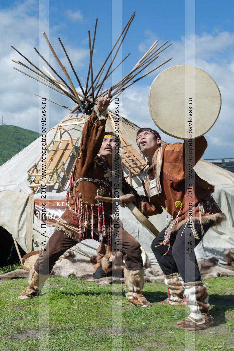 Фотография: мужчины в традиционной одежде коренных жителей исполняют танец с бубнами