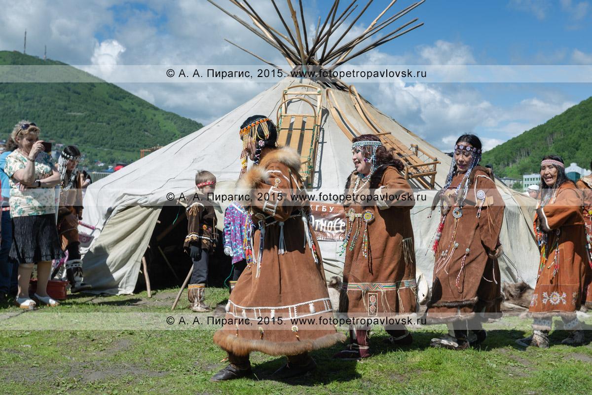 Фотография: женщины в традиционной одежде коренных жителей Камчатки танцуют возле яранги