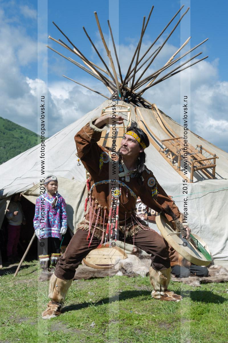 Фотография: мужчина в традиционной одежде коренных жителей Камчатки танцует с бубном возле яранги