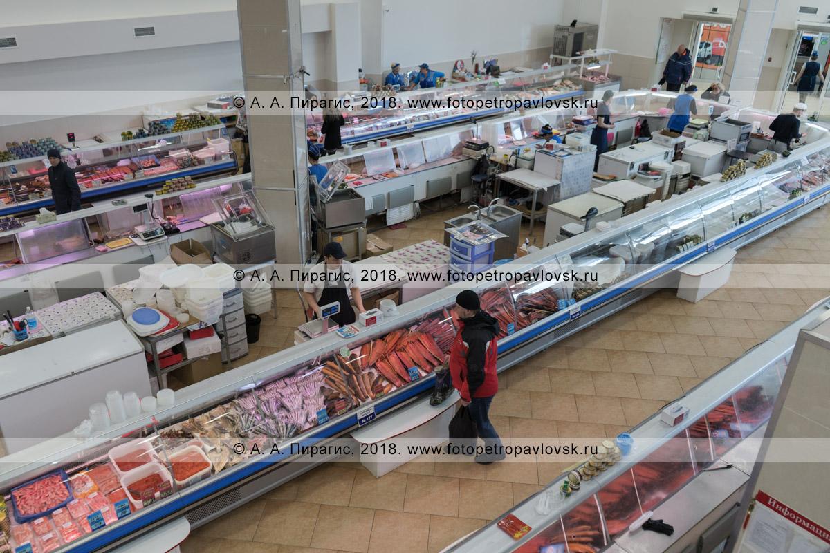 Фотография: вид сверху на торговый зал продуктового рынка, где продается свежая и мороженая рыба, икра лососевых и иных пород рыб, другие деликатесы даров Охотского моря, Берингова моря и Тихого океана