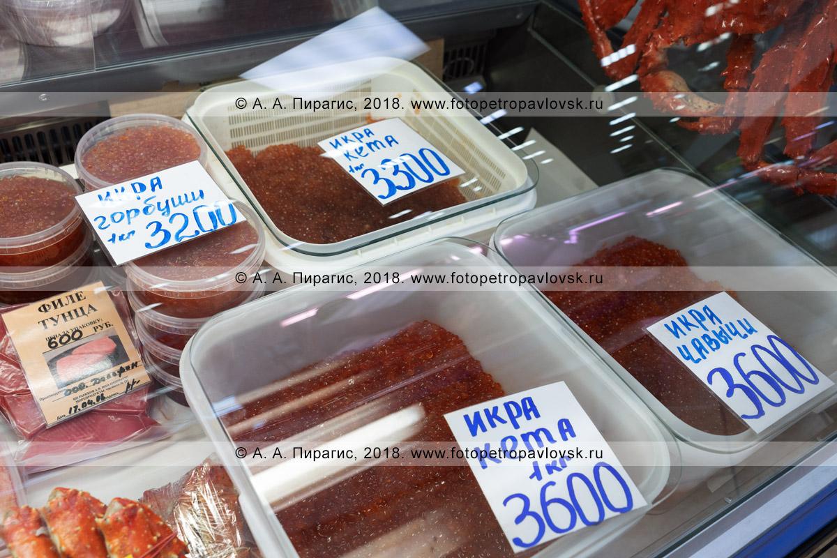 Фотография: торговый прилавок с соленой лососевой (красной) икрой на рыбном рынке, цены на камчатский деликатес: икра горбуши, икра кеты, икра чавычи