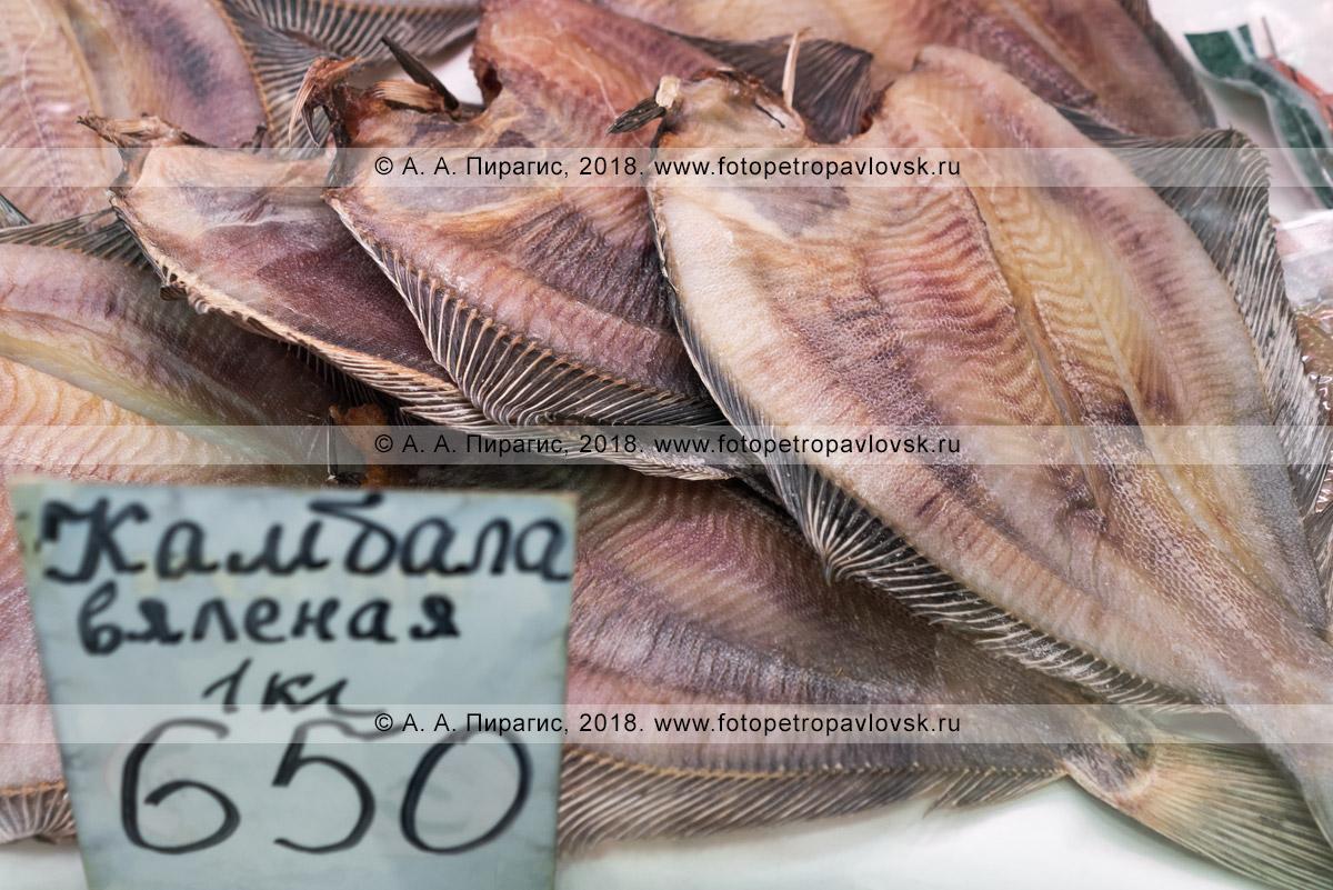 Фотография: торговый прилавок с соленой вяленой рыбой камбала на рыбном рынке, цена на камчатский деликатес