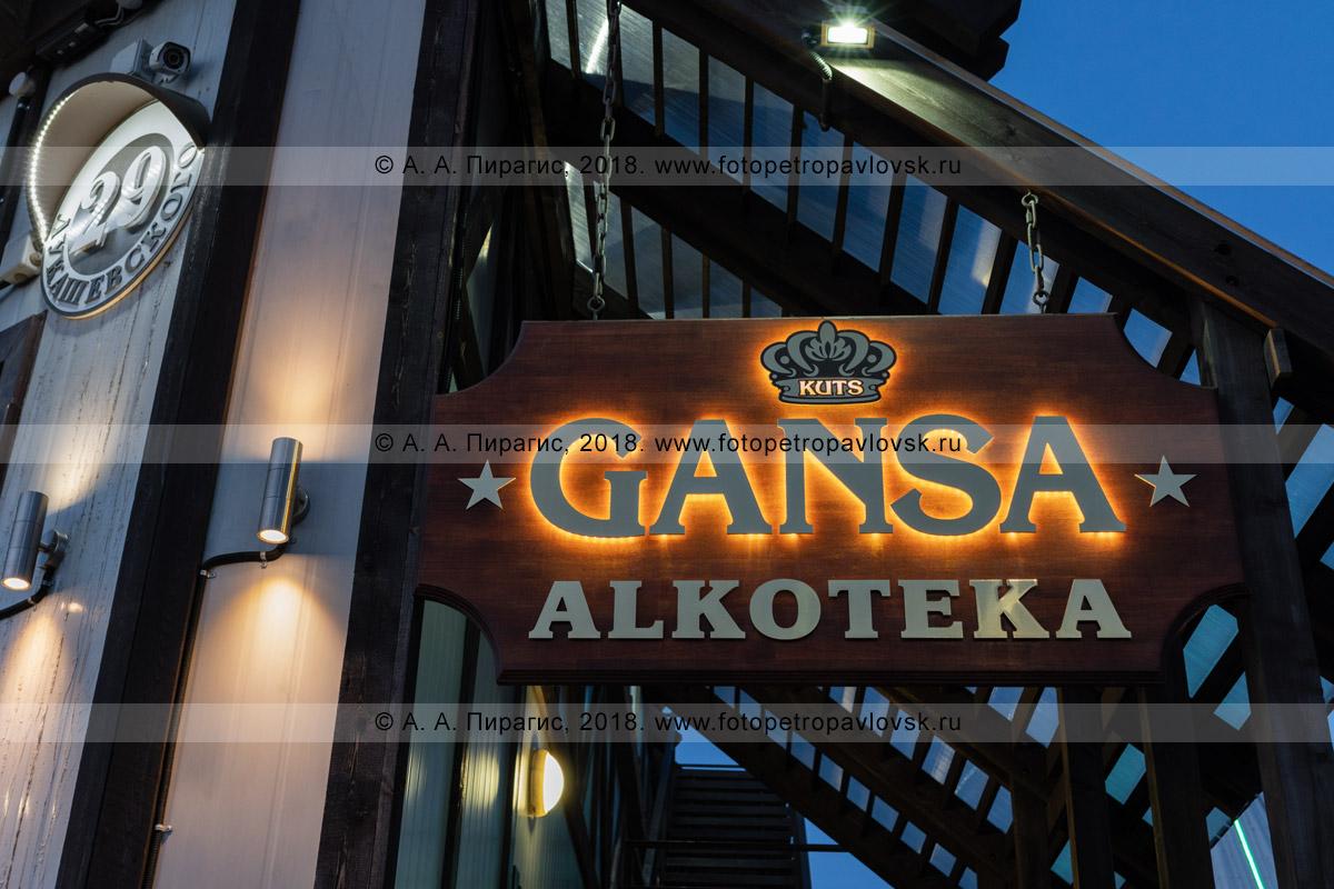 Фотография: деревянная вывеска Gansa Alkoteka, ночная подсветка