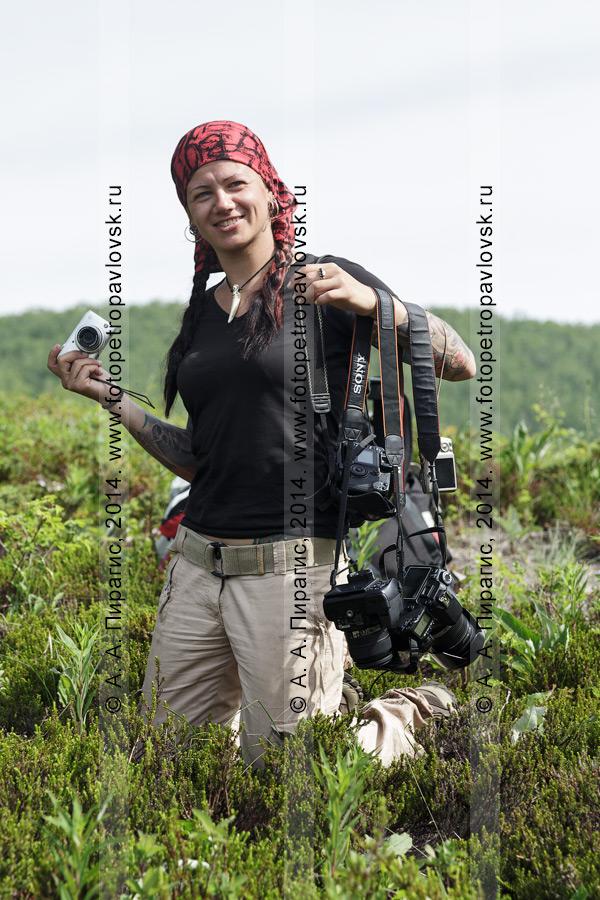 Фотография: улыбающаяся девушка с фотоаппаратами на лоне дикой камчатской природы