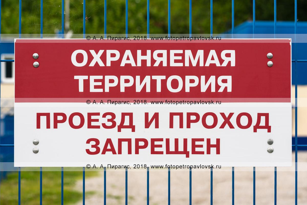 Фотография: запрещающая табличка на заборе, надпись: «Охраняемая территория, проезд и проход запрещен»