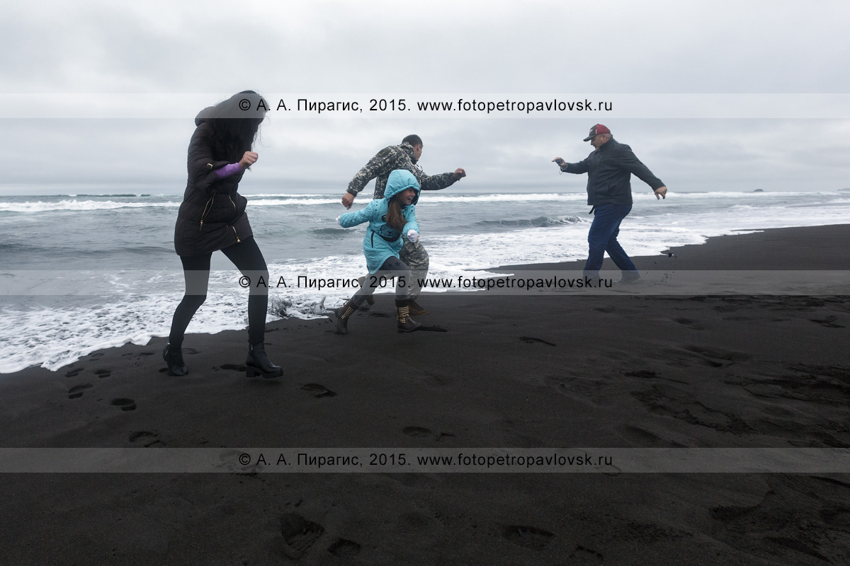 Фотография: Халактырский пляж на Камчатке, туристы убегают от волн Тихого океана. Камчатский край