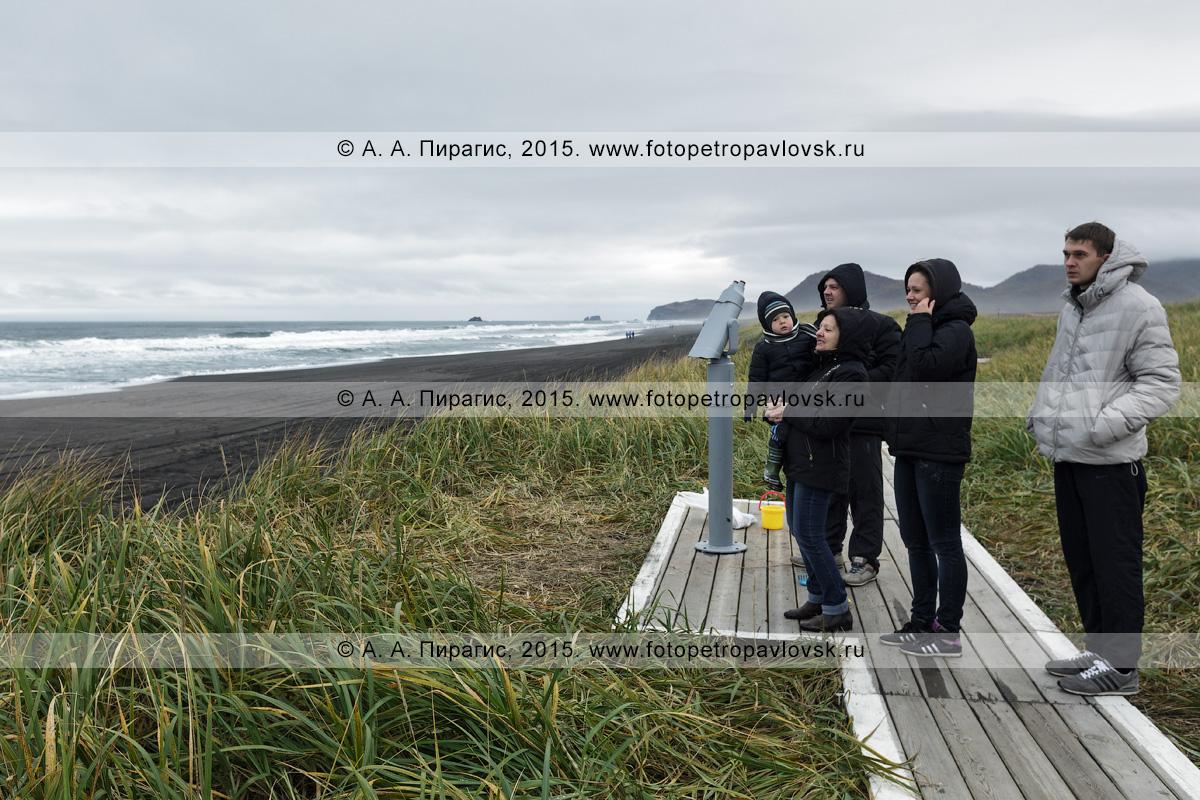 """Фотография: туристический визит-центр """"Халактырский пляж"""", камчатские туристы наслаждаются живописным видом на Тихий океан в пасмурную погоду, стоя возле стационарного обзорного бинокля для осмотра достопримечательностей. Полуостров Камчатка"""