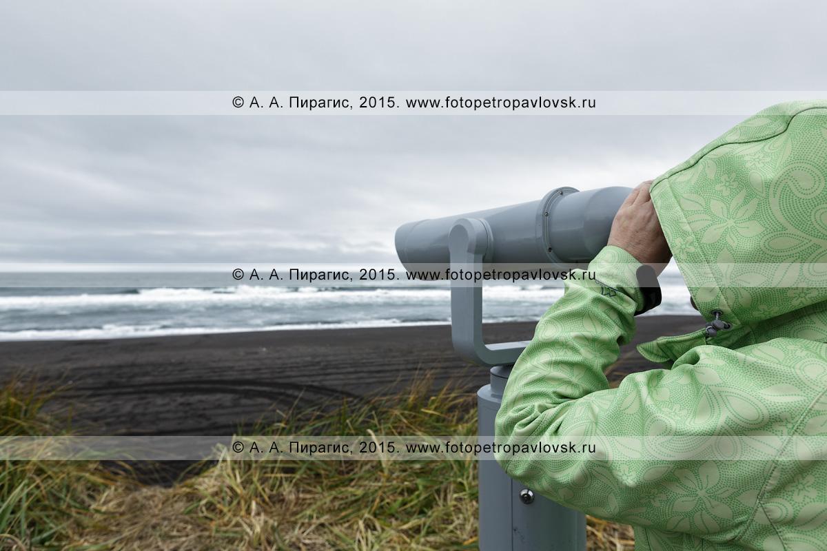 """Фотография: Халактырский пляж на Камчатке, турист смотрит в стационарный обзорный бинокль для осмотра достопримечательностей на волны Тихого океана в пасмурную погоду. Камчатский туристский визит-центр """"Халактырский пляж"""""""