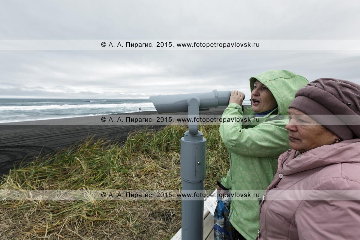 """Фотография: туристский визит-центр """"Халактырский пляж"""", туристы наслаждаются живописным видом на Тихий океан в пасмурную погоду, стоя возле стационарного обзорного бинокля для осмотра достопримечательностей. Полуостров Камчатка"""