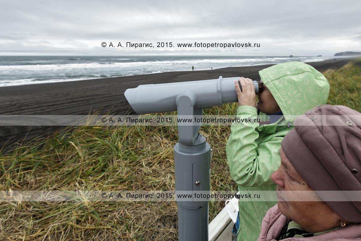 """Фотография: туристы смотрят в стационарный обзорный бинокль для осмотра достопримечательностей на волны Тихого океана в пасмурную погоду. Камчатский туристический визит-центр """"Халактырский пляж"""""""