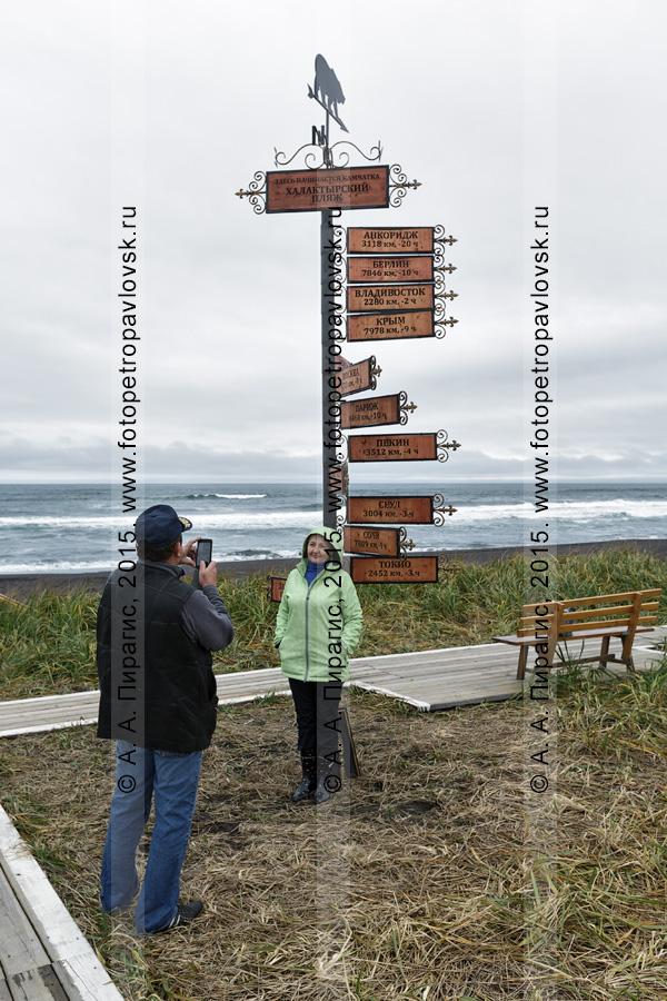 """Фотография: туристы фотографируются на фоне Тихого океана и туристического указателя """"Здесь начинается Камчатка. Халактырский пляж"""". Камчатский край"""