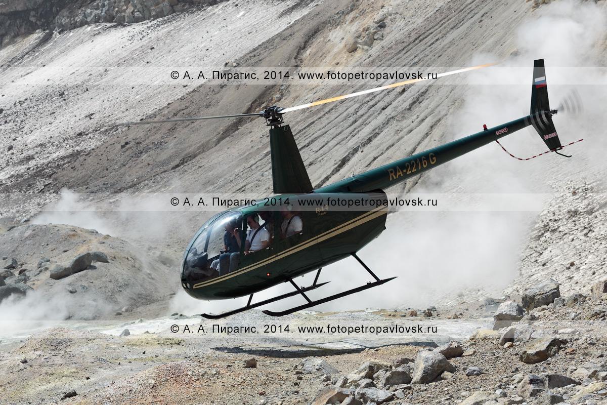 Фотография: вертолет Robinson R44 Raven с туристами и путешественниками на борту взлетает в кратере действующего вулкана Мутновская сопка. Камчатский край, Мутновско-Гореловская группа вулканов