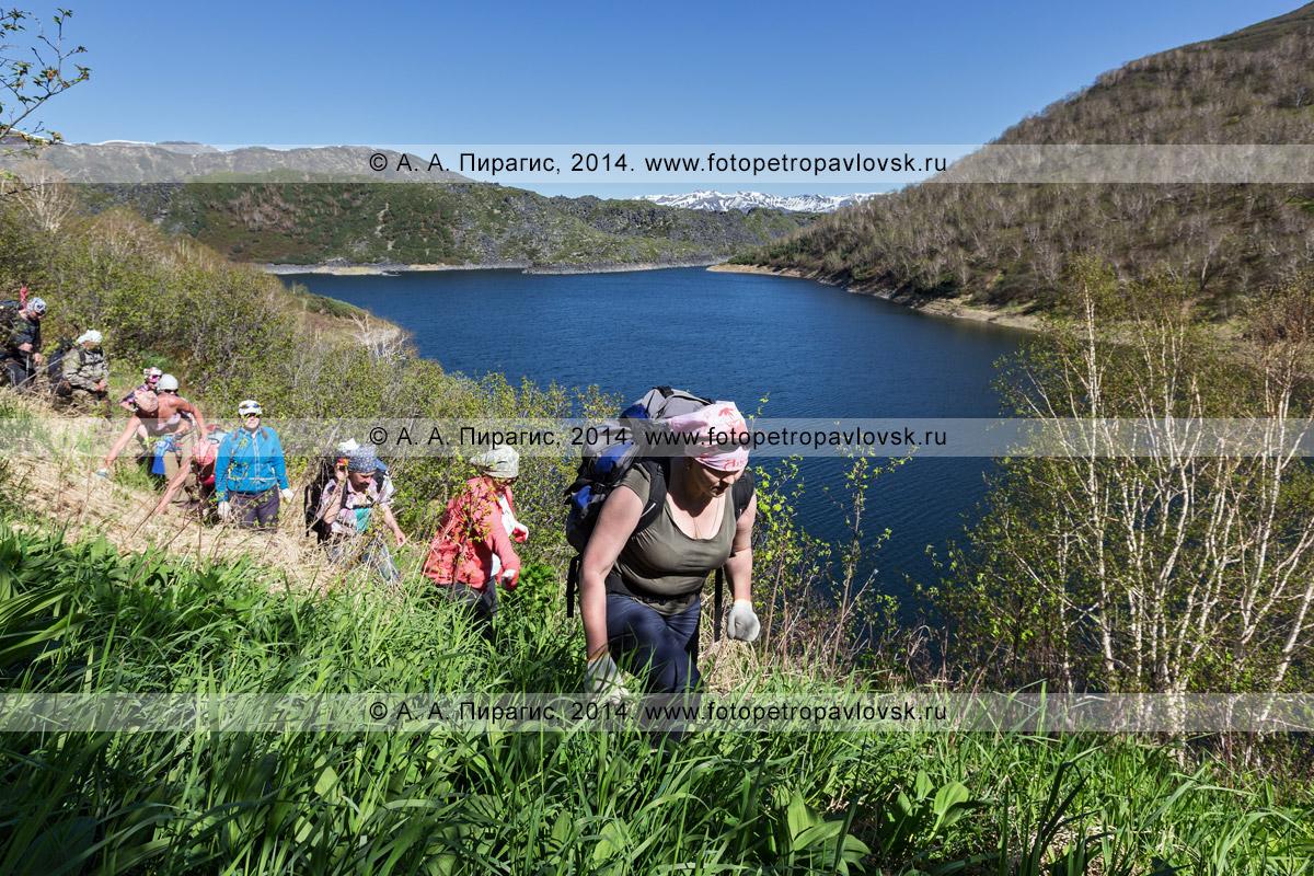 Фотография: камчатские туристы идут по склону сопки, крутому обрыву — берегу озера Ангре на Камчатке