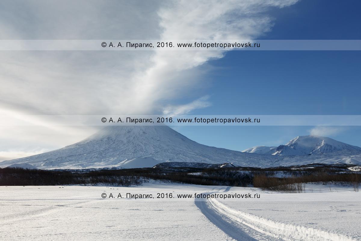 Фотография: активный вулкан Ключевская сопка, извергающий гигантский столб пара и газа, и снегоходная дорога к камчатскому исполину — самому высокому действующему вулкану Евразии