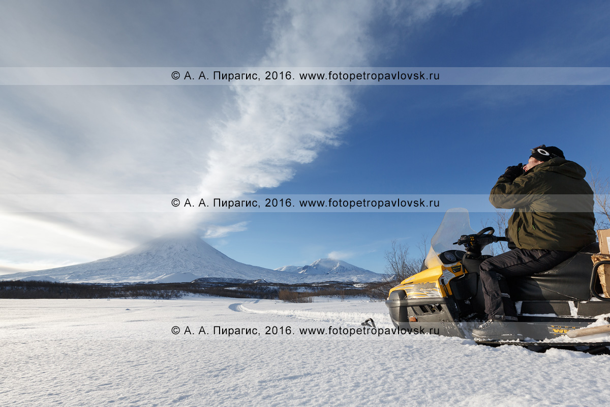 Фотография: камчатский турист и путешественник на снегоходе фотографирует действующий Ключевской вулкан на Камчатке