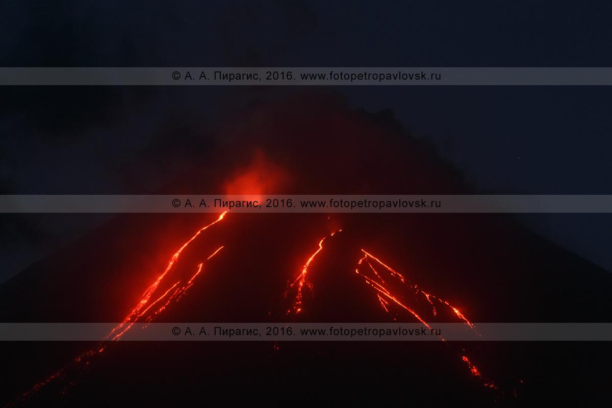 Фотография: ночной вид на извержение вулкана Ключевская сопка (Klyuchevskaya Sopka) и текущие лавовые потоки по склону камчатского исполина