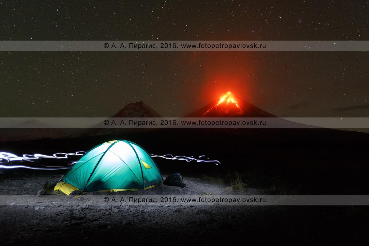 Фотография: туристическая палатка на фоне извержения вулкана Ключевская сопка ночью и свет от налобных фонариков возле палатки. Полуостров Камчатка
