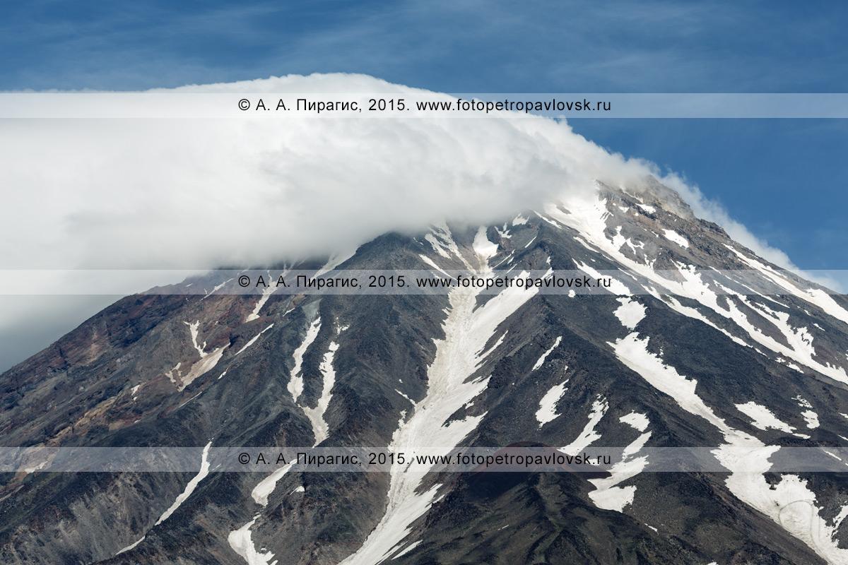 Фотография: вулканический пейзаж полуострова Камчатка — вид на вершину действующего Корякского вулкана (Koryaksky Volcano), частично закрытую облаками. Камчатский край