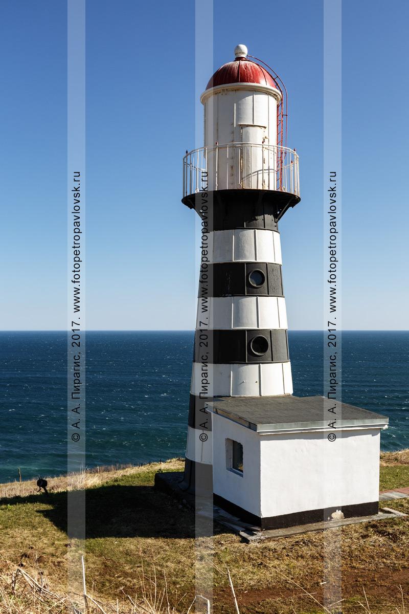 Фотография: камчатский полосатый черно-белый Петропавловский маяк с красной крышей на берегу Авачинского залива в Тихом океане. Полуостров Камчатка