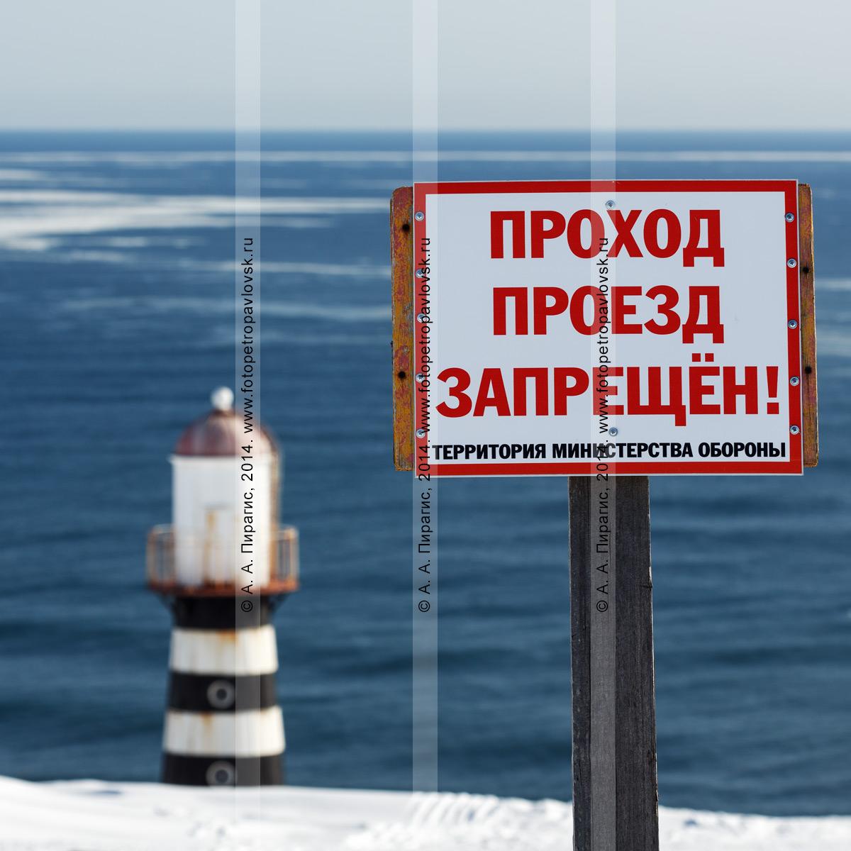 """Фотография: табличка """"Проход, проезд запрещен! Территория Министерства обороны"""" на фоне Петропавловского маяка на берегу Тихого океана. Камчатка"""