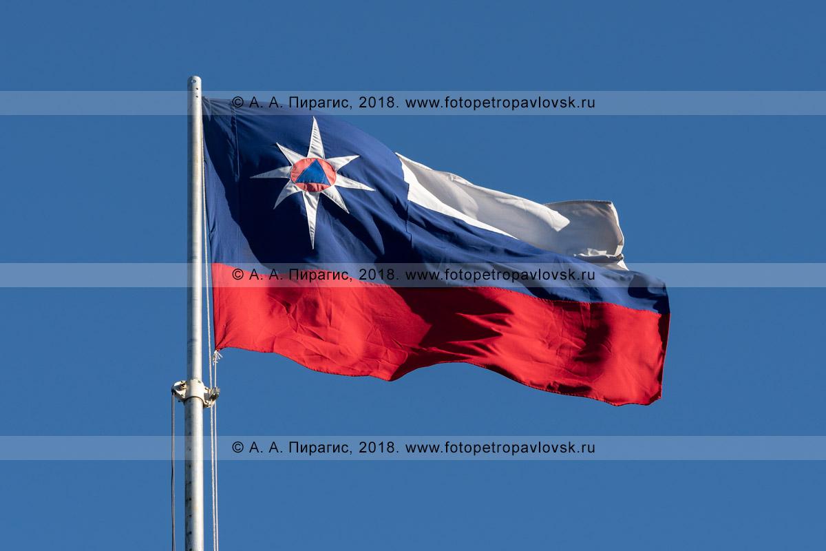 Фотография: флаг c эмблемой Министерства Российской Федерации по делам гражданской обороны, чрезвычайным ситуациям и ликвидации последствий стихийных бедствий развевается на ветру в солнечную погоду на фоне синего неба