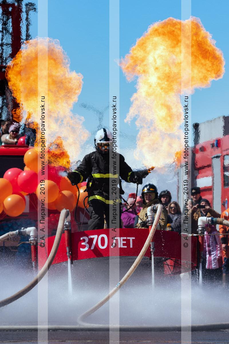 Фотография: пожарный-спасатель МЧС России с огнеметами в руках, парящий на платформе, которая удерживает камчатского огнеборца над землей сильным напором воды из пожарных рукавов