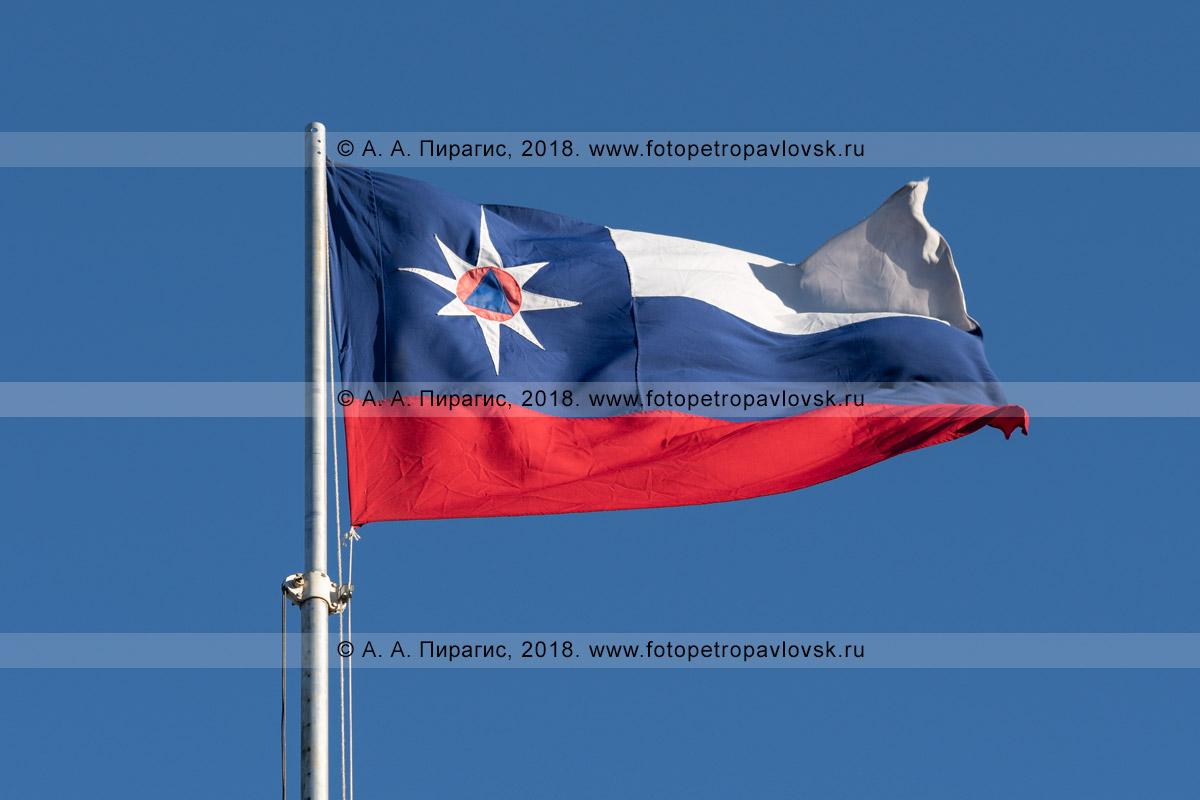 Фотография: официальный флаг МЧС России развевается на ветру в ясную солнечную погоду на фоне голубого неба