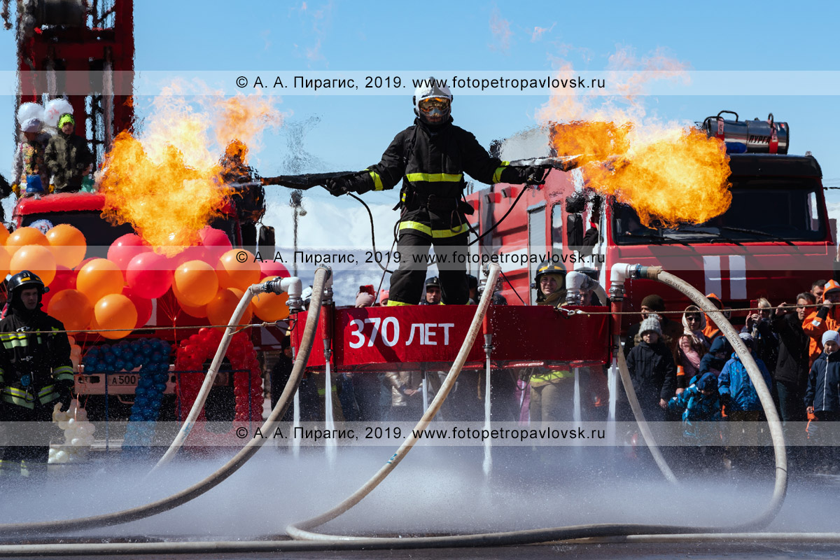 Фотография: смелый камчатский пожарный-спасатель МЧС России с огнеметами, извергающими пламя и одновременно летающий на платформе, которая удерживает огнеборца в воздухе силой воды, подаваемой из пожарного автомобиля по пожарным напорным рукавам и бьющей в землю
