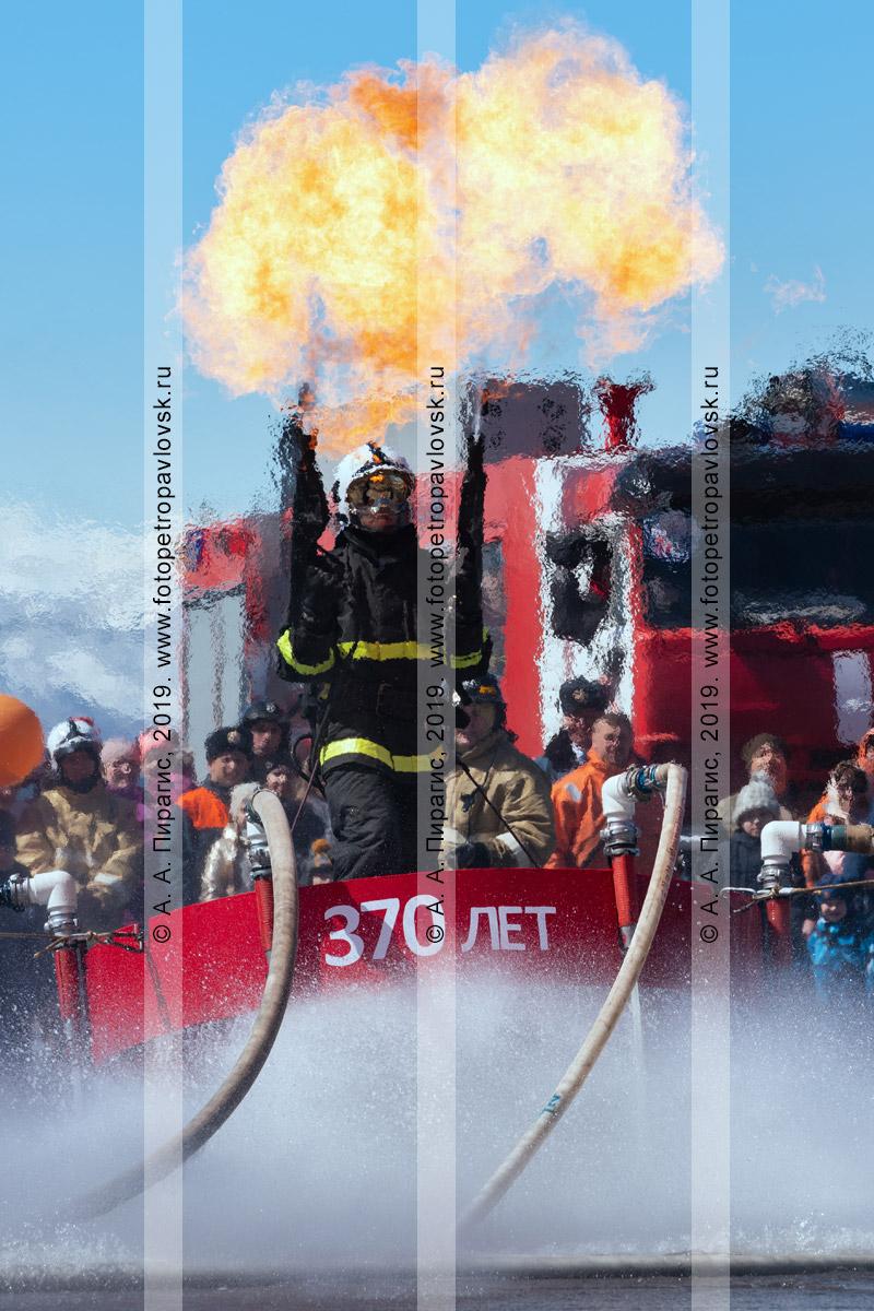 Фотография: камчатский пожарный-спасатель МЧС России с двумя огнеметами в руках, летающий на платформе, которая удерживает огнеборца в воздухе сильным напором воды из пожарных рукавов