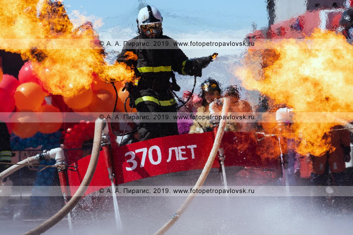 Фотография: камчатский пожарный-спасатель МЧС России с парой огнеметов в руках, летающий на платформе, которая удерживает огнеборца в воздухе сильным напором воды из пожарных рукавов