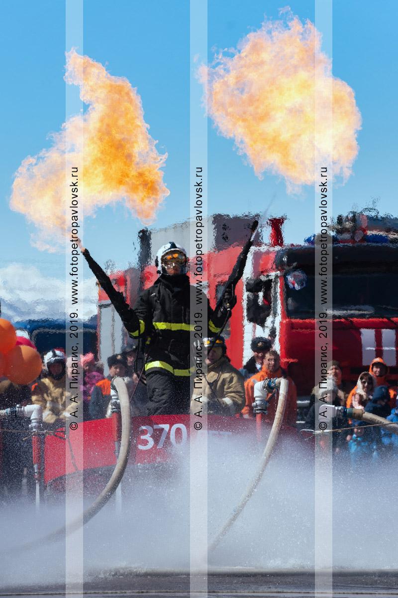 Фотография: камчатский пожарный-спасатель МЧС России с огнеметами в руках, парящий над землей на платформе, которая удерживает огнеборца в воздухе сильным напором воды из пожарных рукавов