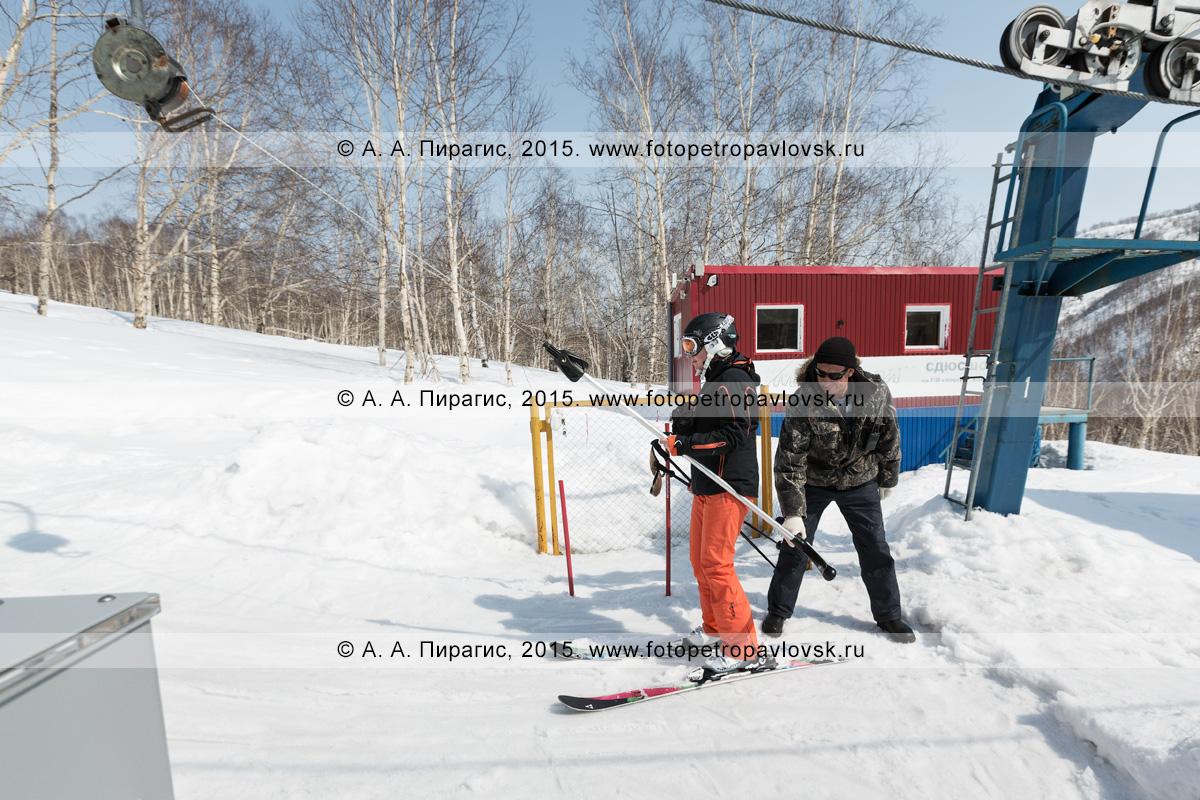 """Фотография: сотрудник горнолыжной базы """"Морозная"""" помогает девушке горнолыжнице на бугельном подъемнике. Камчатка, город Елизово, гора Морозная, горнолыжная база """"Морозная"""""""
