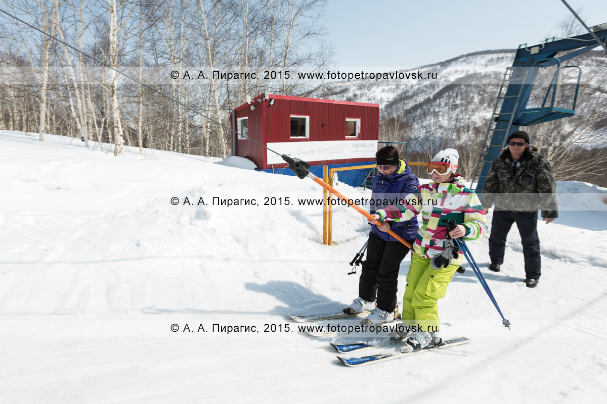 """Фотография: горнолыжная база """"Морозная"""", две девушки-горнолыжницы едут на бугельном подъемнике на гору Морозную. Камчатский край, город Елизово"""