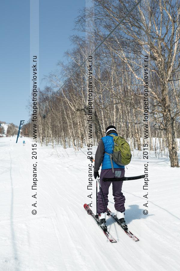 """Фотография: горнолыжник с рюкзаком едет на бугельном подъемнике на горе Морозной (горнолыжная база """"Морозная""""). Камчатский край, город Елизово"""
