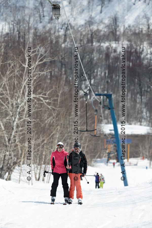 """Фотография: горнолыжная база """"Морозная"""", две девушки-горнолыжницы поднимаются на бугельном подъемнике на гору Морозную. Город Елизово, Камчатка"""