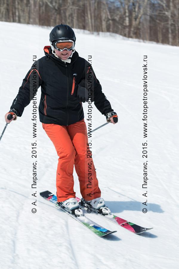 """Фотография: улыбающаяся девушка-горнолыжница спускается с горы Морозной. Горнолыжный спорт на полуострове Камчатка. Елизовский район, город Елизово, горнолыжная база """"Морозная"""""""