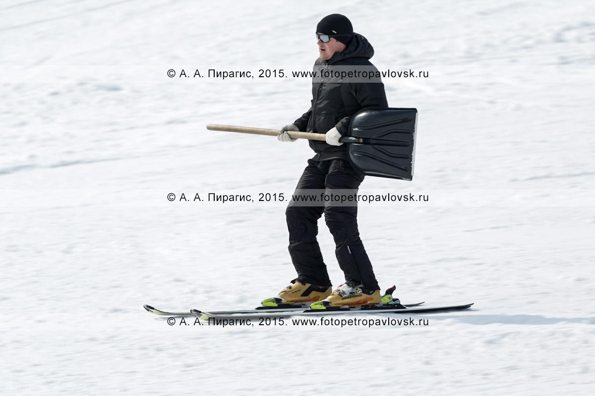 """Фотография: горнолыжная база """"Морозная"""", горнолыжник едет на лыжах с лопатой в руках по склону горы Морозной. Город Елизово, Елизовский район, Камчатский край"""