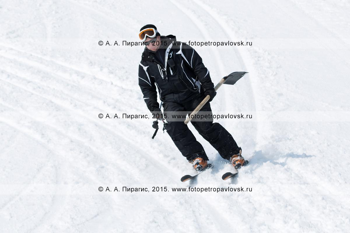 """Фотография: горнолыжная база """"Морозная"""", горнолыжник едет на лыжах с лопатой в руке по склону горы Морозной. Город Елизово, Елизовский район Камчатского края"""