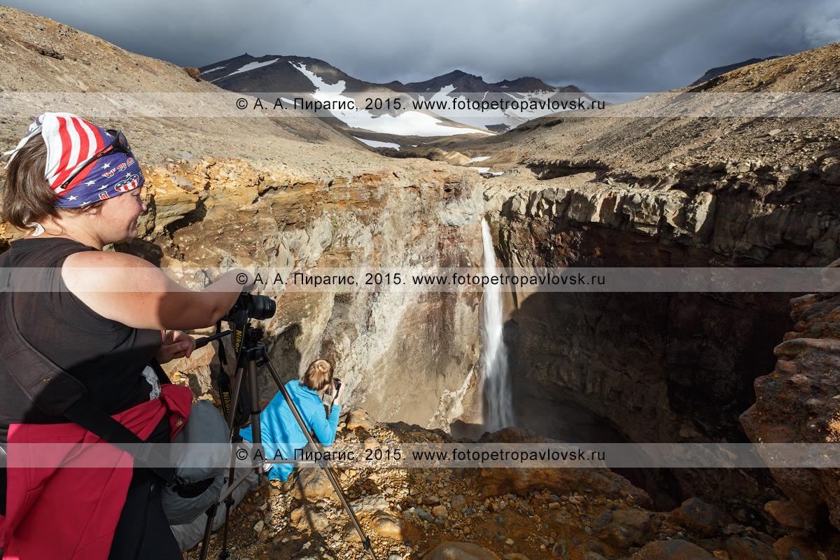 Фотография: девушки-туристки фотографируют 80-метровый водопад на реке Вулканной в каньоне (овраге) Опасном на действующем вулкане Мутновская сопка. Камчатский край