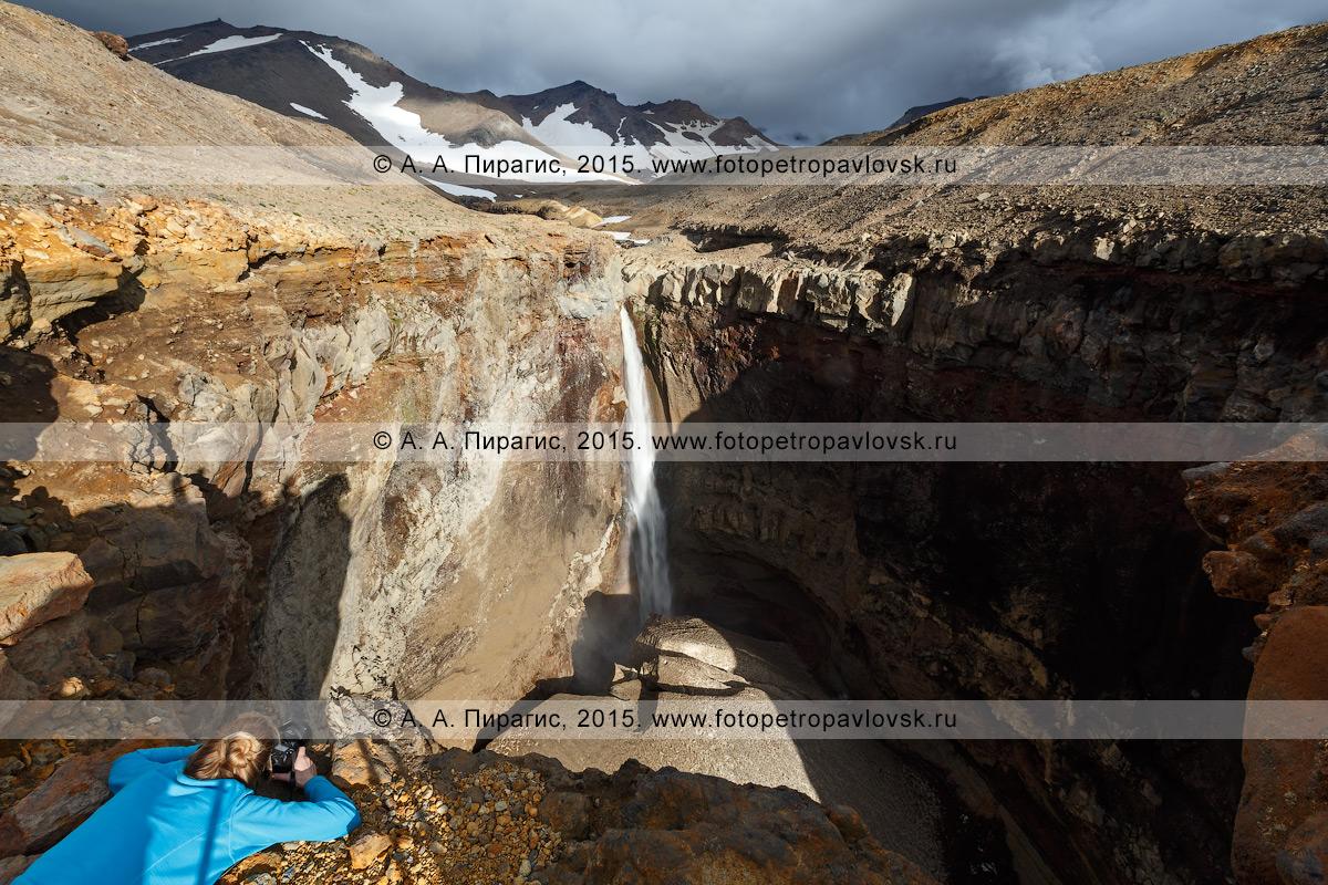Фотография: девушка-туристка фотографирует 80-метровый водопад, низвергающийся с уступа лавового плато в овраг Опасный (каньон Опасный) на Мутновском вулкане. Камчатка