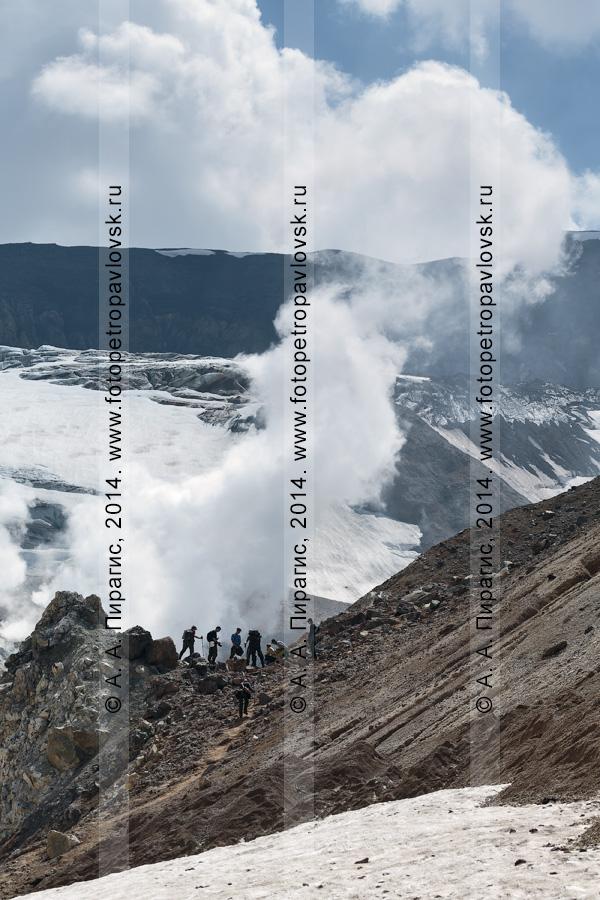 Фотография: пеший туризм в Камчатском крае — туристическая группа в кратере действующего вулкана Мутновская сопка на фоне активной фумарольной деятельности вулкана. Камчатка, Мутновско-Гореловская группа вулканов