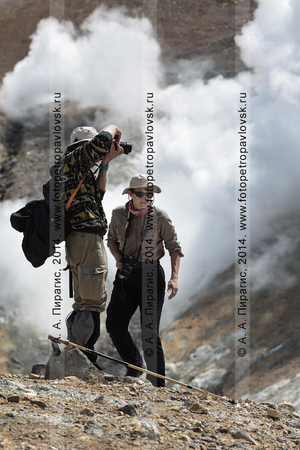 Фотография: туризм на полуострове Камчатка — туристы и путешественники фотографируют в кратере действующего Мутновского вулкана на фоне мощной фумарольной активности вулкана. Камчатский край, Мутновско-Гореловская группа вулканов