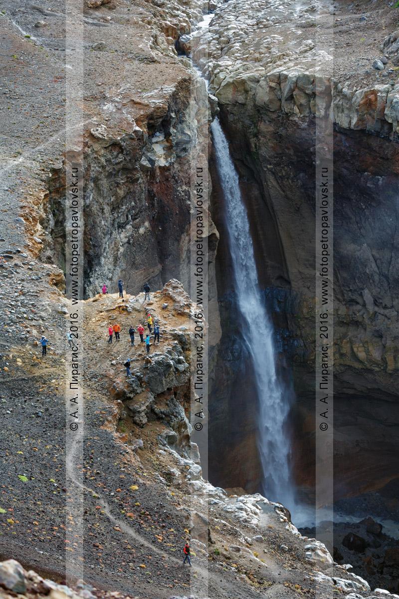 Фотография: туристы и путешественники гуляют в каньоне Опасном (овраг Опасный), наслаждаются живописным видом на мощный водопад, низвергающийся с уступа лавового плато действующего Мутновского вулкана