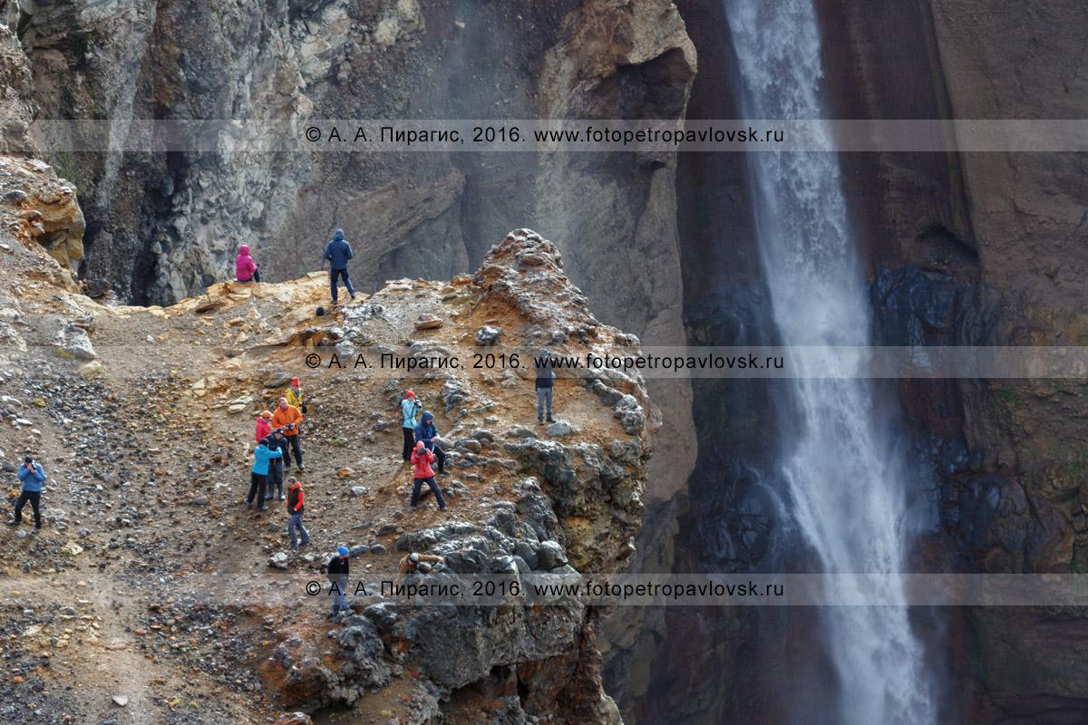 Фотография: туристы и путешественники фотографируются возле водопада во время экскурсии в овраг Опасный (каньон Опасный), расположенный у подножия действующего вулкана Мутновская сопка