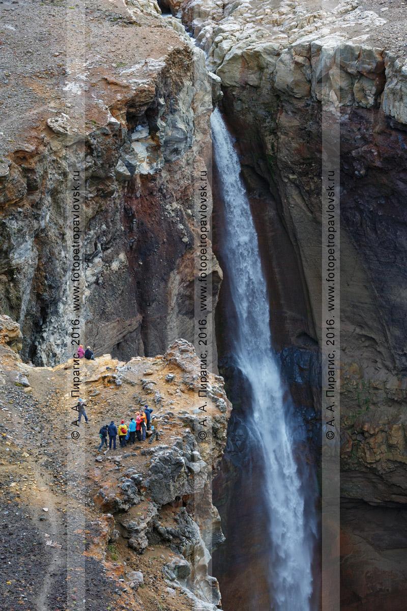 Фотография: туристическая группа фотографируется возле живописного водопада, низвергающегося с уступа лавового плато в овраг Опасный (каньон Опасный) на Мутновском вулкане