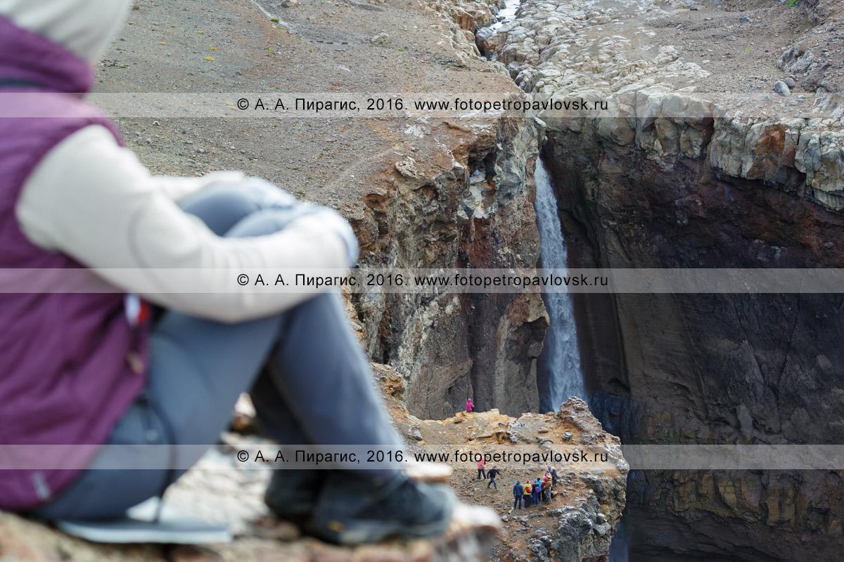 Фотография: путешественники на туристической экскурсии на величественном водопаде в овраге Опасном (каньон Опасный) на вулкане Мутновская сопка