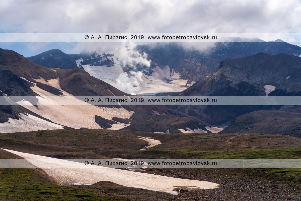 Фотография: вид на действующий Мутновский вулкан, вырывающийся из кратера пар и газ, высокогорную тундру и снежники у подножия огнедышащей горы