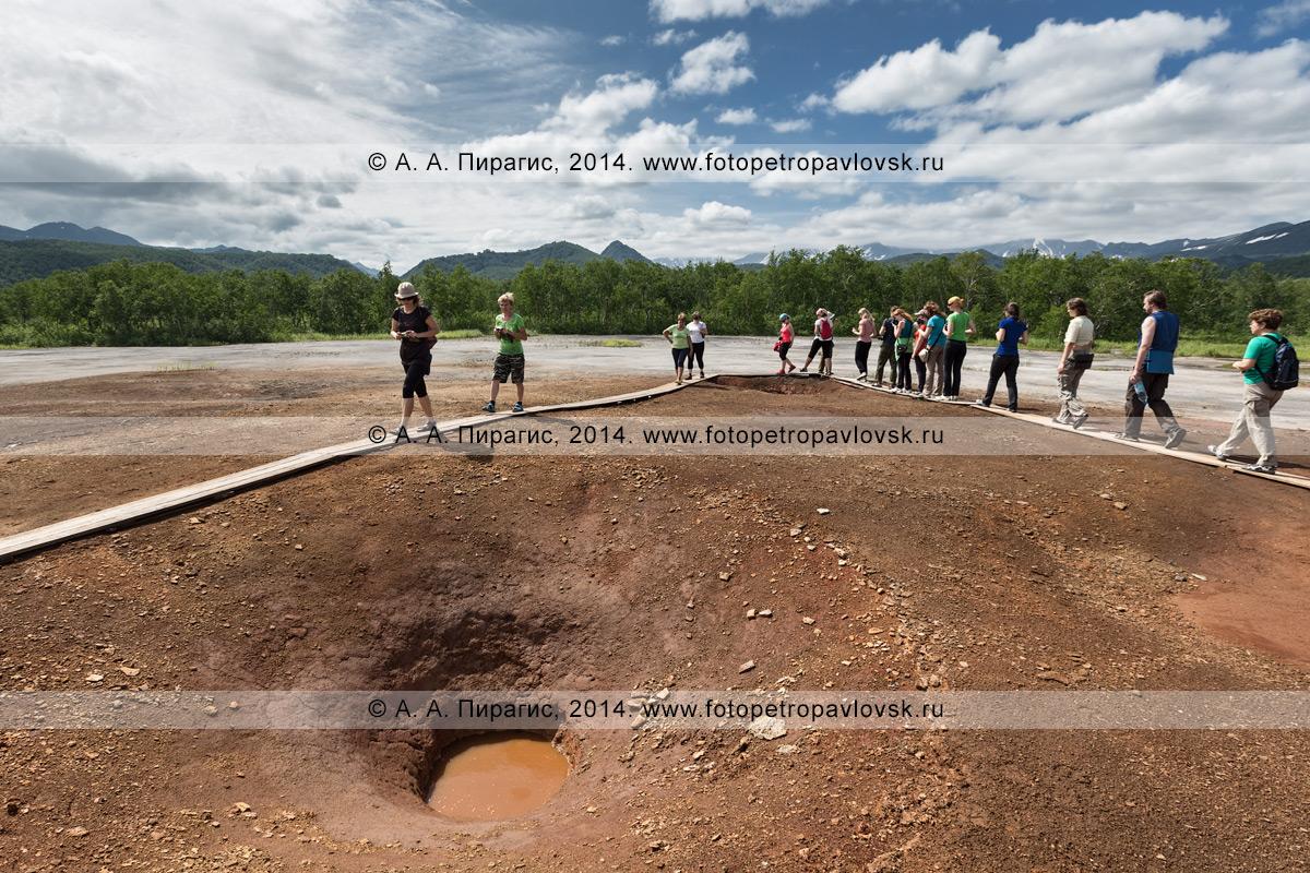 Группа туристов и путешественников гуляет по травертиновому щиту Котел (термальная площадка Котел) вокруг грифонов с термальной водой. Камчатка, Налычевский природный парк